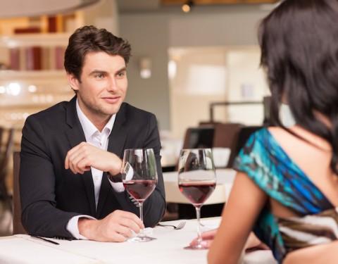 Seducing  handsome man looking at beautiful dark hair woman with wine glasses. Romantic and love mood