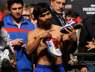 LAS VEGAS, NV - NOVEMBER 11: Boxer Manny Pacquiao appears on stage and points to his NIKE shoes during the official weigh-in for his bout against Juan Manuel Marquez at the MGM Grand Garden Arena November 11, 2011 in Las Vegas, Nevada. Pacquiao will defend his WBO welterweight title against Marquez when the two meet in the ring for the third time on November 12 in Las Vegas. (Photo by Ethan Miller/Getty Images)