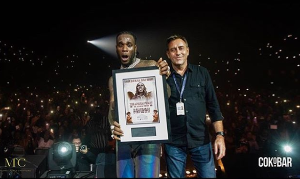 """Burna Boy had a great night yesterday November 3, as he became the first Afrobeat artiste to sell out the SSE Arena asides winning the """"Best African Act' Award at the star-studded 2019 MTV EMA held in Seville, Spain. The sold out concert which was held at the 12,500-seat SSE Arena also had Davido, Dave, M.anifest,ij Wstrn and Stormzy performing. Here is a photo of Burna Boy receiving a plaque over the sold-out concert and videos from the event;"""