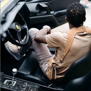 Nigerian superstar, Ayodeji Balogun, professionally known as Wizkid shares a jaw-dropping photo of himself chilling in his Ferrari Sports car with a 'million dollar' holster fastened to his arms and his fellow celebrities are amazed.